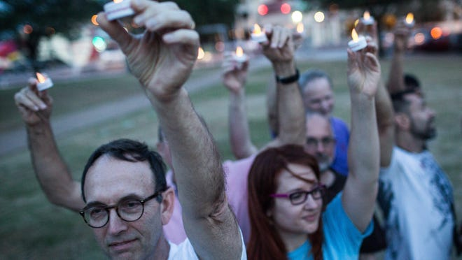 In this 2014 file photo, community members stand in the shape of a ribbon and raise candles at the AIDS Candlelight Memorial Service at Republic Square Park in Austin.