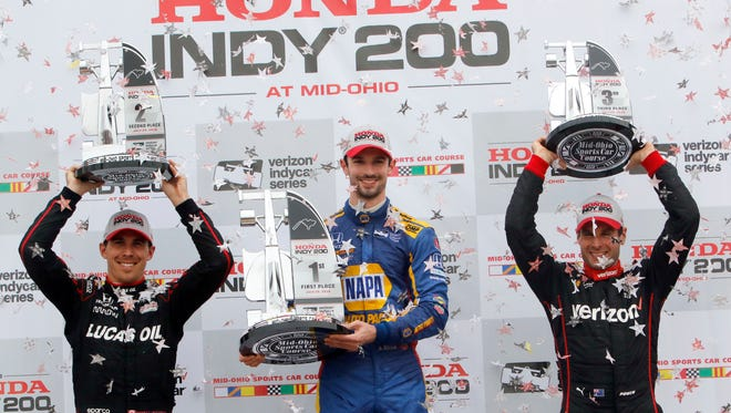 Robert Wickens, left, hoists the second place trophy while Alexander Rossi, center, holds the first place trophy and Will Power hoists the third place trophy in victory lane after winning the IndyCar Series auto race, Sunday, July 29, 2018, at Mid-Ohio Sports Car Course in Lexington, Ohio.