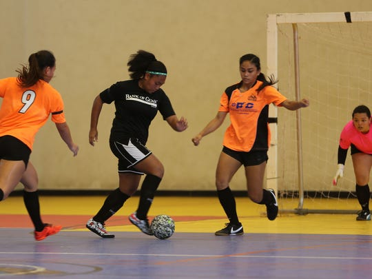 Bank of Guam Lady Strykers' Jinae Teria looks for an opportunity to shoot the ball as Personal Finance Center Lady Crushers' Colleen Naden (No. 9) and Kaeliana Taitano (right) close in on her on defense in a Week 6 match of the Bud Light Women's Futsal League Sunday at the Guam Sports Complex gym. The Lady Crushers won 6-2.
