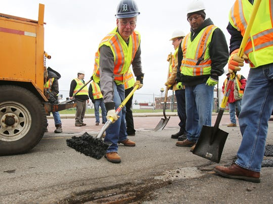 Gov. Rick Snyder, left,  assists MDOT workers along Michigan Ave. near Trumbull to patch potholes Thursday, April 23, 2015 in Detroit.