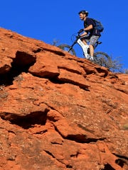 A mountain biker climbs the Church Rocks Trail in the Red Cliffs Desert Reserve north of Washington City.