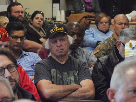 U.S. Army veteran Tom Dean (center) listens to remarks