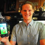 Hogan's Irish Bar is a Pokestop. The designation has been good for business, bringing people into the bar. Patrick shows a Gastly that just showed up on his phone.