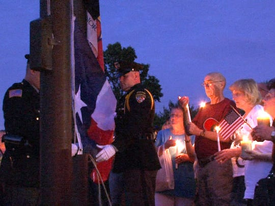 People hold candles outside the Monmouth County Police Academy Monday evening, July 11, 2016, as the Texas state flag is raised during a remembrance of the 5 Dallas officers who were killed last week.