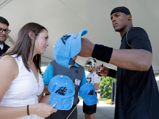 Carolina Panthers' Cam Newton signs autographs for guests after a practice during the NFL team's minicamp in Charlotte, N.C., Thursday, June 18, 2015. (AP Photo/Chuck Burton)
