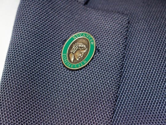 """Mladen Stoev of Bay Colony Golf Club sports his green """"Advanced Sommelier"""" pin."""