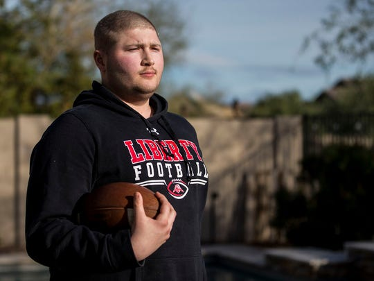 Zach Hunzinger poses for a portrait on Monday, Feb. 4, 2019, at his home in Peoria, Ariz. Hunzinger, an offensive lineman for Liberty High School, was diagnosed with bone cancer but has since been told that he is cancer-free.