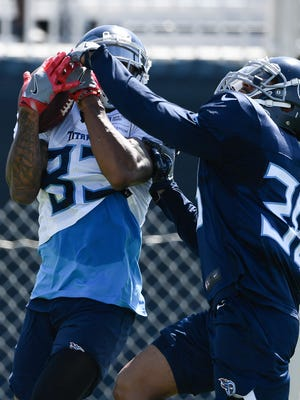 Titans wide receiver Devin Ross (83) pulls in a pass over cornerback Joseph Este (38) during a training camp practice Monday at Saint Thomas Sports Park.