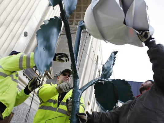 This Chris Dunn file photos shows York workers Harry Frey, Roy Wolfhope and David Rudolph connecting cables to the city's white rose on Friday, Dec. 30, 2011. This year's New Year's Eve celebration remains a question.