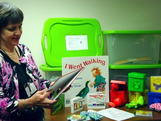 Lisa Schmittle, York County Libraries' children's program manager, looks through books and other educational items that are part of the traveling story time trunk about colors, which will rotate through six libraries this fall. (SUBMITTED PHOTO)