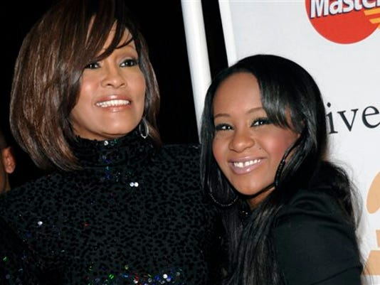 FILE - In this Feb. 12, 2011, file photo, singer Whitney Houston, left, and daughter Bobbi Kristina Brown arrive at an event in Beverly Hills, Calif. Brown, who was in hospice after months of receiving medical care, died on Sunday, July 26, 2015.