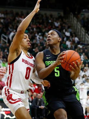 Michigan State guard Cassius Winston (5) looks to shoot as Wisconsin guard D'Mitrik Trice (0) defends during the second half of an NCAA college basketball game, Friday, Jan. 17, 2020, in East Lansing, Mich.