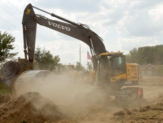 An excavator moves dirt on property just east of the