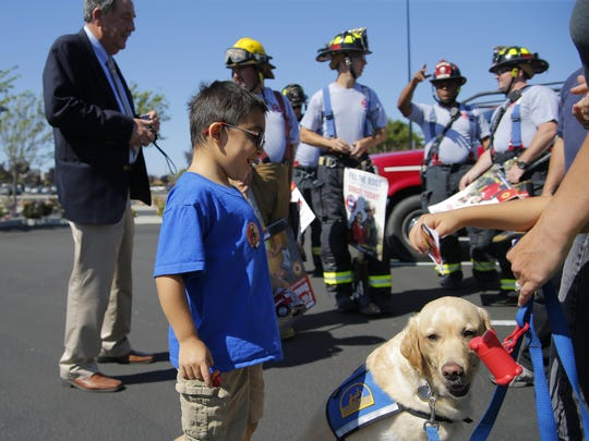 Nicholas Archdeacon, 8, of Salinas, who is attending MDA Summer Camp thanks to the money raised during Fill the Boot drive, hangs out with local firefighters Friday on North Davis Road in Salinas.