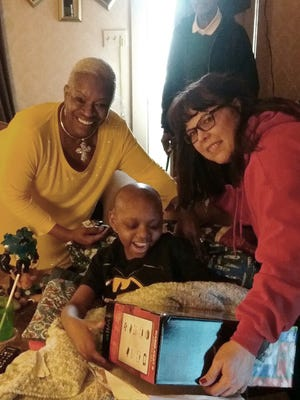 Savion smiles as he receives a Wii from Yvette Smallwood and Theresa Palmer of the Marie Generette Missionary Society.