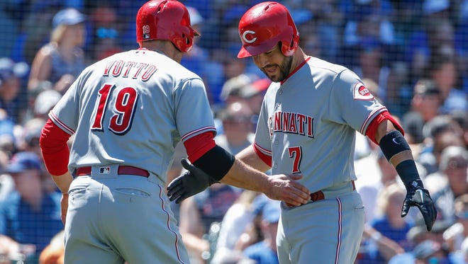 Cincinnati Reds third baseman Eugenio Suarez (7) celebrates with first baseman Joey Votto (19) after scoring against the Chicago Cubs during the fourth inning at Wrigley Field on Sunday, July 8, 2018.