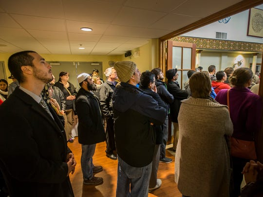 Attendees listen to speakers from the lobby as hundreds of people gather at the Islamic Society of Delaware for an interfaith service on Monday night.