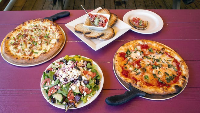 Clockwise from left, the Drunken Clam pizza, bruschetta, Rose's pizza and Greek salad at Fresh West.