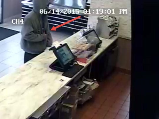 This frame from video surveillance shows the suspect revealing a gun.