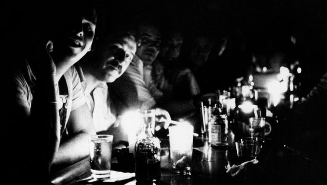 People at Chapman's Restaurant in midtown Manhattan continue their drinking by candlelight after New York City had a blackout on July 13, 1977.