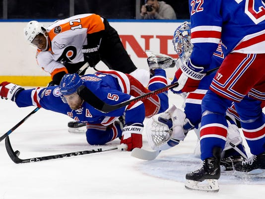 New York Rangers defenseman Dan Girardi (5) tries to clear the puck as he helps goalie Henrik Lundqvist (30) defend the goal against Philadelphia Flyers right wing Wayne Simmonds (17) during the first period of an NHL hockey game, Sunday, April 2, 2017, in New York. (AP Photo/Julie Jacobson)