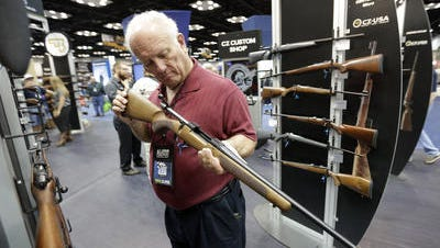 Jerry Miller, of Georgetown, Texas, looks over a rifle at the National Rifle Association's annual convention in Friday, April 25, 2014 in Indianapolis.
