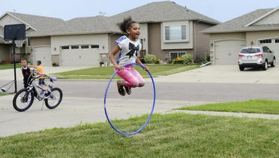 Kierra Dunlap plays with a hula-hoop outside her family home in far western Sioux Falls this summer. The neighborhood is divided with some houses falling in the Sioux Falls School district, including the two houses on the left side of the photo and others fall in the Tea School district including the one on the right side of the photo and the Dunlaps'.