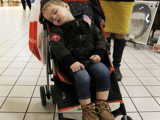 Morrison Newcomer, 2, sleeps in his stroller as his