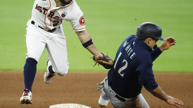 Houston Astros second baseman Jose Altuve, left, catches Seattle Mariners' Evan White trying to steal in the top of the seventh inning Sunday, Aug. 16, 2020, in Houston.