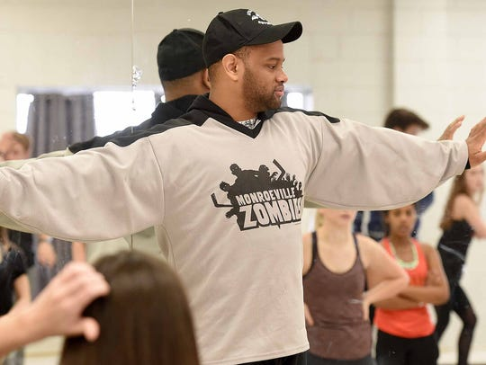 Choreographer Dexter Bishop, a 2004 graduate and three-year Attaché member, goes over dance moves with the group during a recent practice at Clinton High School.