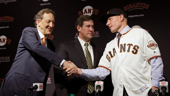 San Francisco Giants pitcher Mark Melancon, right, shakes hands with CEO Larry Baer, left, during his introduction Friday, Dec. 9, 2016, in San Francisco. Melancon recently signed with the Giants after pitching for the Washington Nationals last season. Giants general manager Bobby Evans, center, looks on.