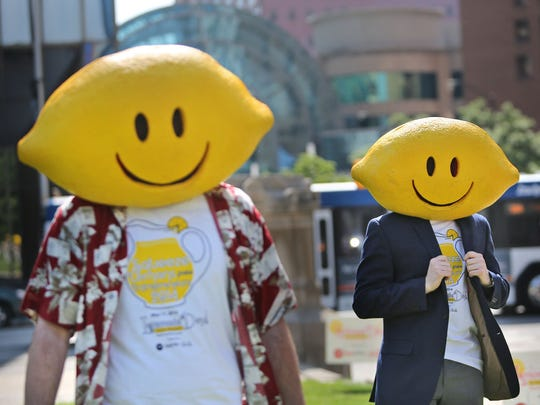 Volunteers Devin Smith (left) and Brenden Davidson encourage passersby to stop for a glass of lemonade during Lemonade Day at the Statehouse last year.