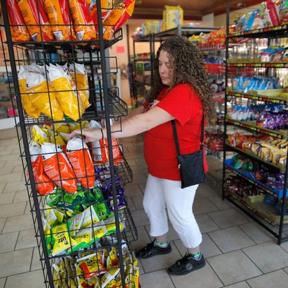 Worker Sarah Coons stocks inventory on the shelves
