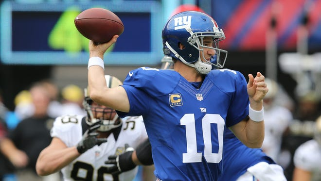 New York Giants quarterback Eli Manning (10) throws a pass as New Orleans Saints' Paul Kruger (99) rushes him during the first half of an NFL football game Sunday, Sept. 18, 2016, in East Rutherford, N.J.