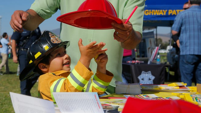 Greyson Dinyari, 3, reaches for another plastic fire hat during the National Night Out celebration in Salinas on Tuesday.