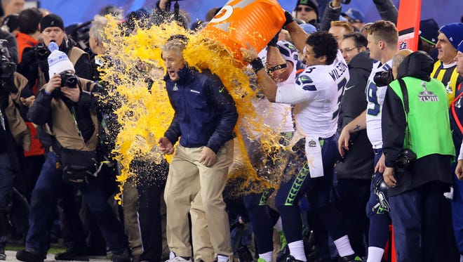 Seattle Seahawks head coach Pete Carroll gets gatorade dump on him by quarterback Russell Wilson (3) during the second half against the Denver Broncos in Super Bowl XLVIII at MetLife Stadium.