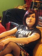 Sasha Mowen, a transgender woman, lounges on her couch