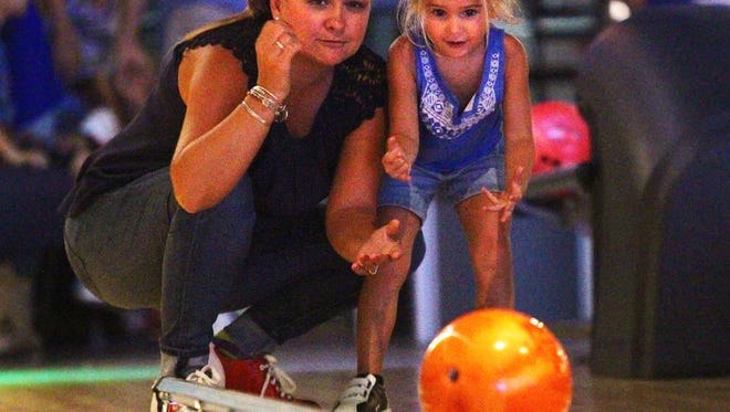 Diana Lurie, of Fort Myers, helps her daughter Brooklyn, 3, roll her bowling ball at Head Pinz in Fort Myers, Florida, on Monday, July 20, 2015.