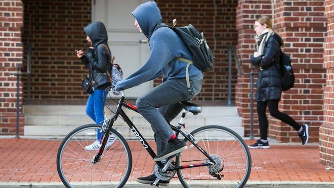 A biker rolls along South College Avenue in Newark.