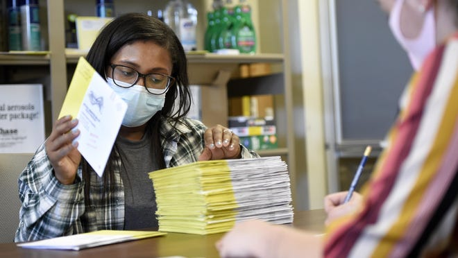 Richmond County Board of Elections workers Arnisha Atkinson, left, and Karissa Howard audit and batch absentee ballots before they are loaded into a machine to be counted at the Board of Elections office in Augusta, Ga., Friday morning October 23, 2020.