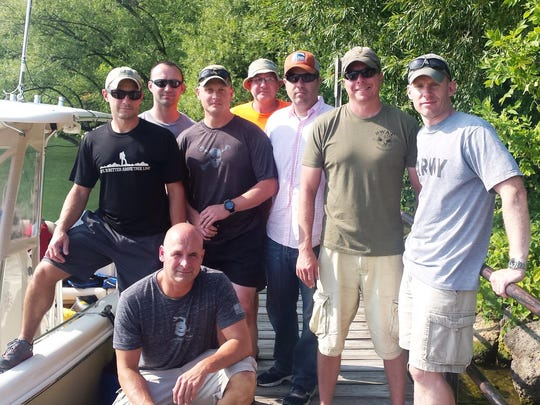 Rochester police sergeant Brett Sobieraski, front, is surrounded by friends who supported the 49-year-old as he swam 32 miles across Lake Ontario last weekend.