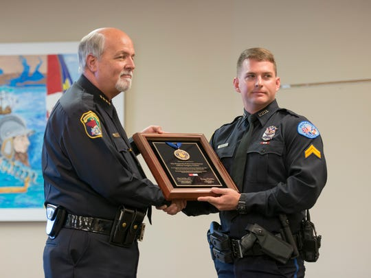 Pensacola Police Department Officer Greg Gomez, right, received a life-saving award at a city of Pensacola employee recognition ceremony in June 2017. Gomez was honored for pulling a suicidal woman down from a bridge months earlier.