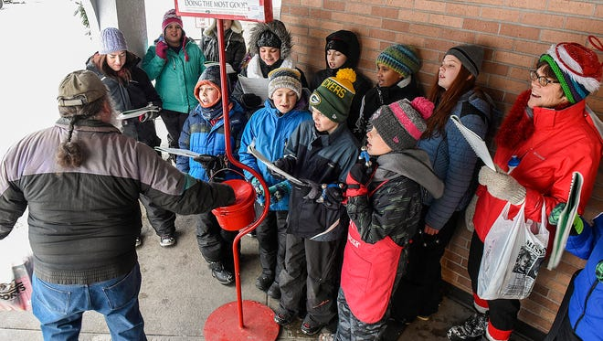 Sixth-grade students from All Saints Academy sing carols and ring the bell to gather donations for The Salvation Army red kettle Monday, Dec. 12, at the Coborn's in Centennial Plaza.