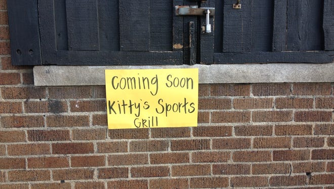 "A sign on the former Head First Sports Cafe reads ""Coming soon: Kitty's Sports Grill."""