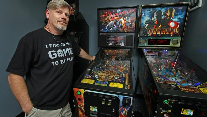Owner Byron Smith poses with a couple of his pinball machines Thursday afternoon, Oct. 1, 2020, at CityCade on South Oakland Street in Gastonia.