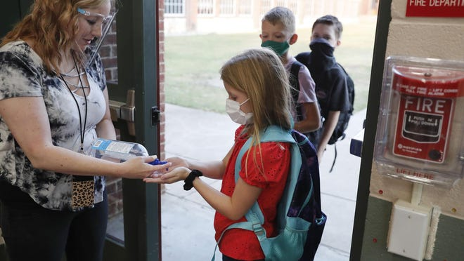 In this Aug. 5, 2020, photo, wearing masks to prevent the spread of COVID19, elementary school students use hand sanitizer before entering school for classes in Godley, Texas. As schools reopen around the country, their ability to quickly identify and contain coronavirus outbreaks before they get out of hand is about to be put to the test.