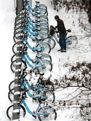 A Divvy bicycle rider deposits his bike in a rental