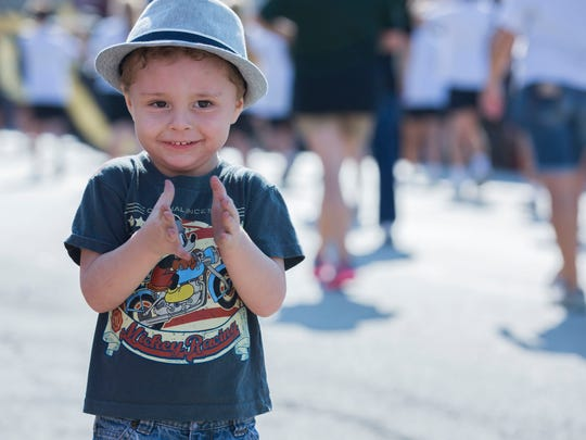 Blake Montgomery, 3, claps as the Labor Day parade passes by him in Boonville on Monday morning.