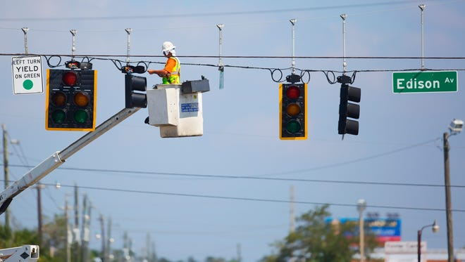 KINFAY MOROTI/THE NEWS-PRESS… Crews work to restore power on Sunday to street signals, homes and businesses throughout Southwest Florida.