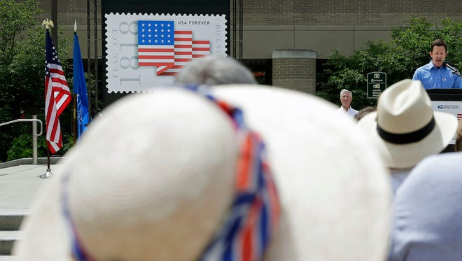 Joanne Delforge of Appleton is attired in patriotic colors while listening to parade committee member, Corey Otis, as the Postal Service holds a dedication ceremony before the 68th annual Flag Day Parade to release a new stamp that celebrates the 200th anniversary of the Flag Act of 1818. The event took place Saturday in Houdini Plaza in Appleton.
